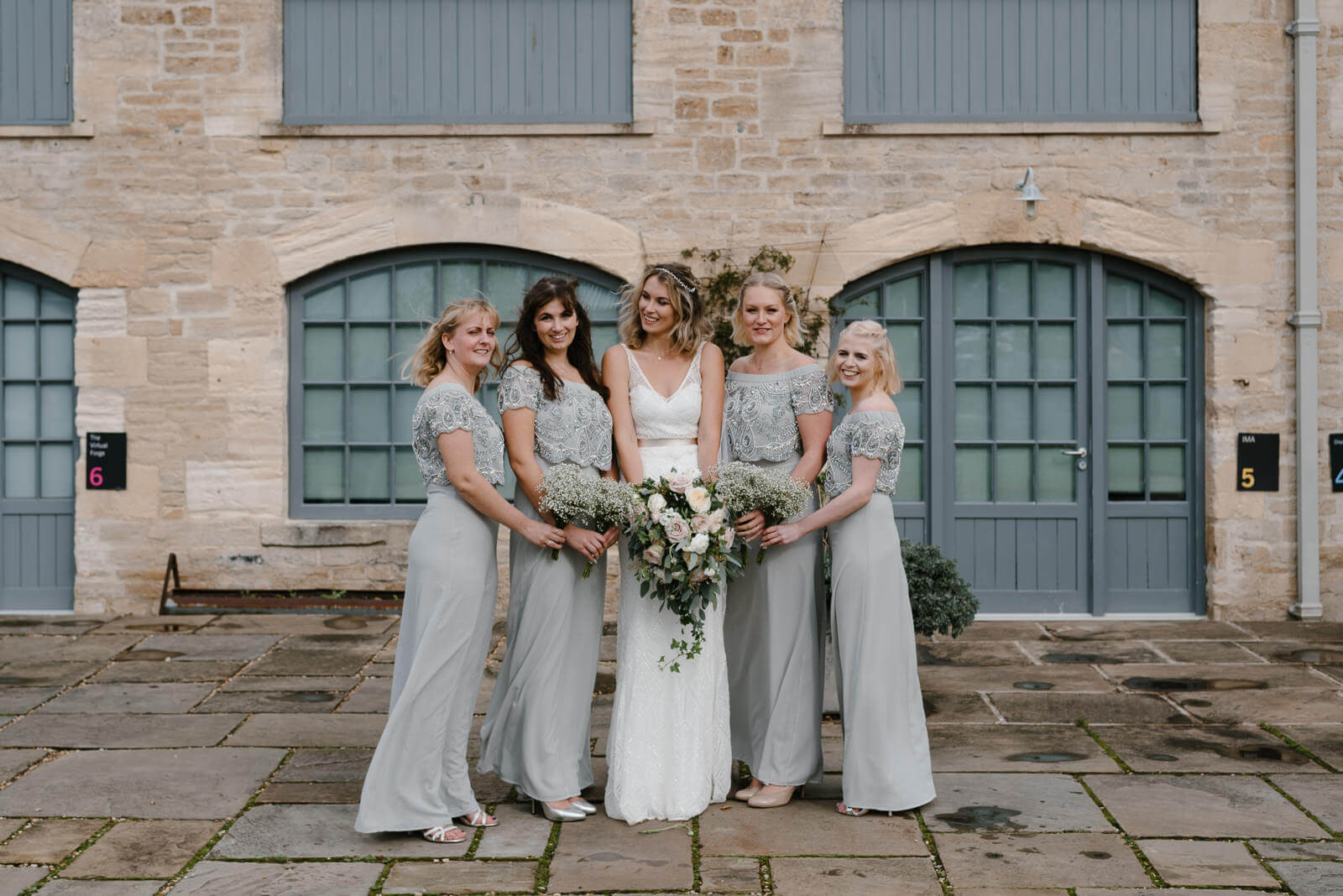 Portrait of bride and her bridesmaids outside Wiltshire Wedding venue in Holt