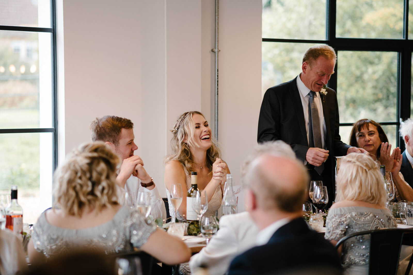 bride laughing during her dads speech at their Wiltshire wedding