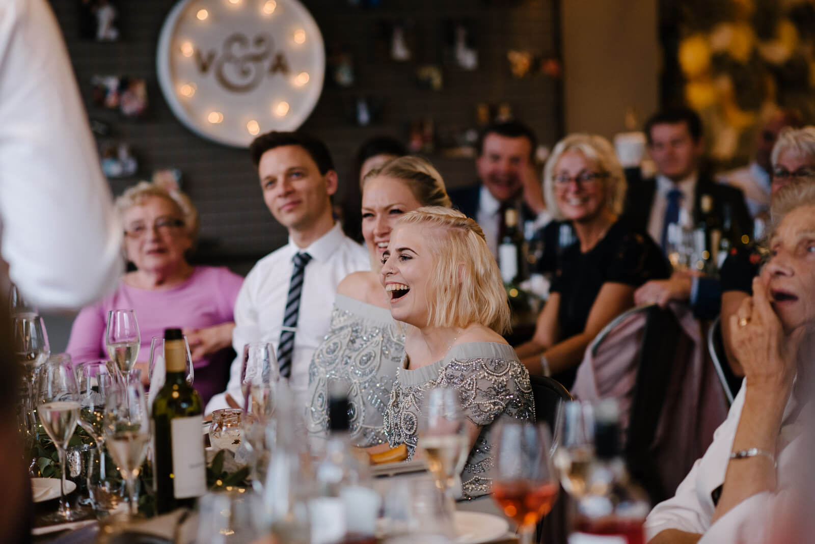 family and friends look on laughing during speeches at Glove Factory Studios in Holt