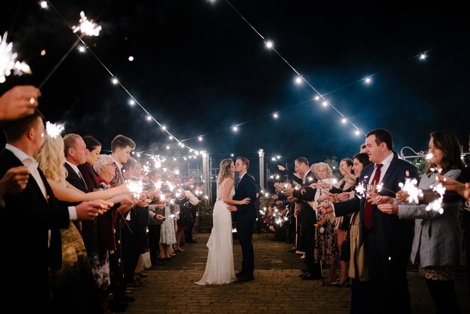 Wiltshire bride and groom kiss under festoon lights during sparklers