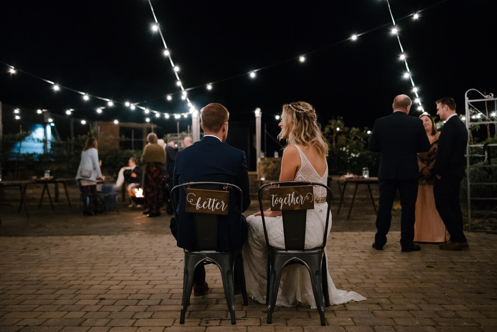 bride and groom sitting on chairs with 'better togethe