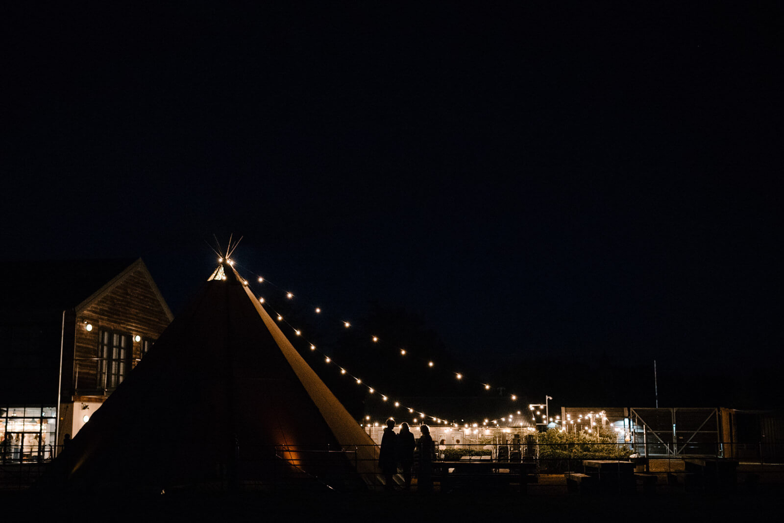 Festoon lighting glows at Glove Factory Studios Wedding in Wiltshire