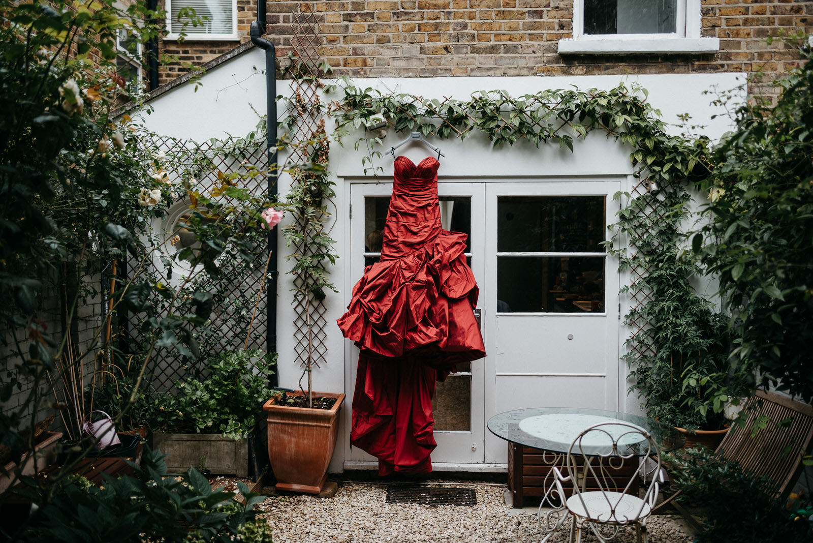 alternative and unique red taffeta wedding dress hanging on wall of London AirBNB
