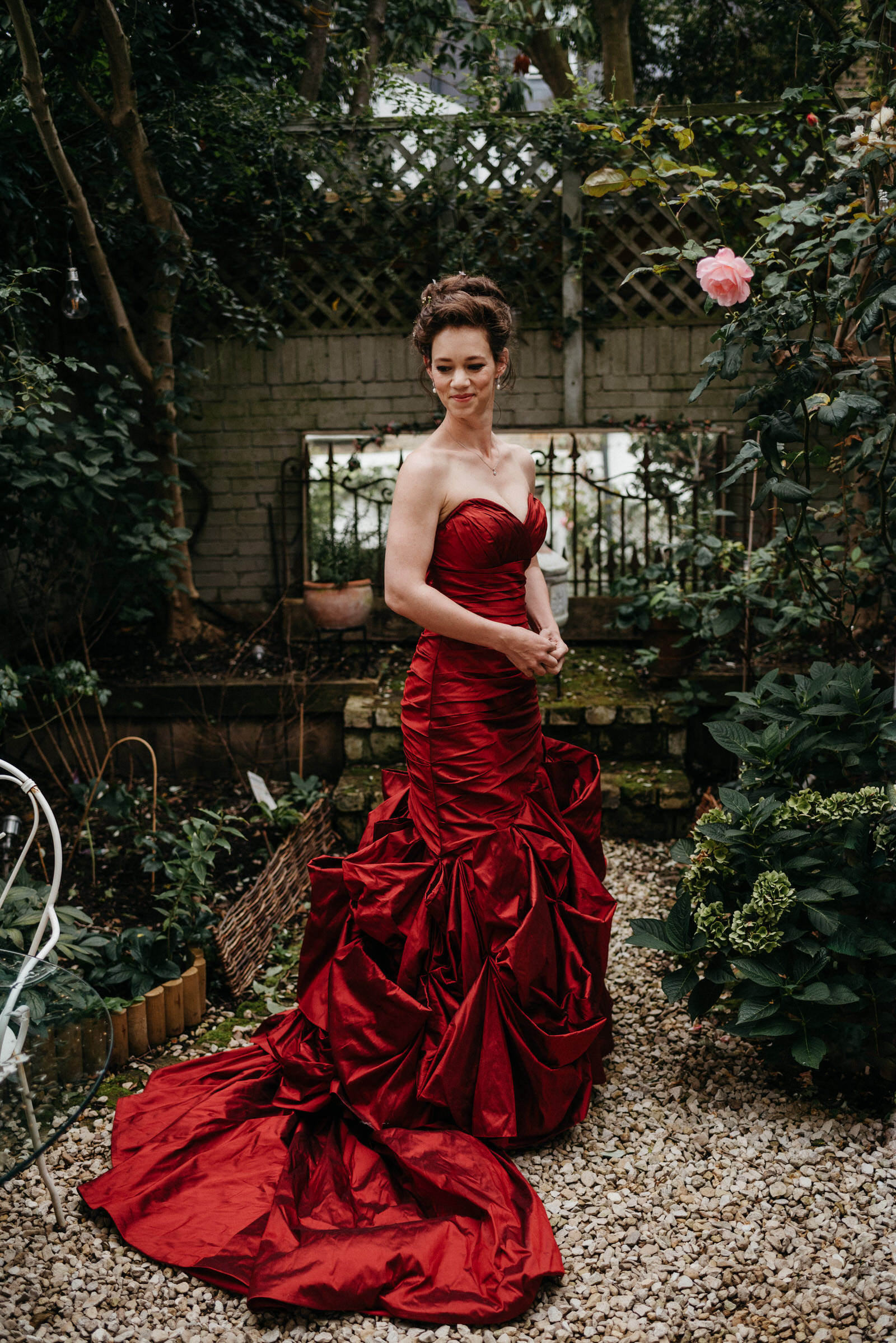portrait of bride wearing her alternative red taffeta wedding dress in Battersea Garden