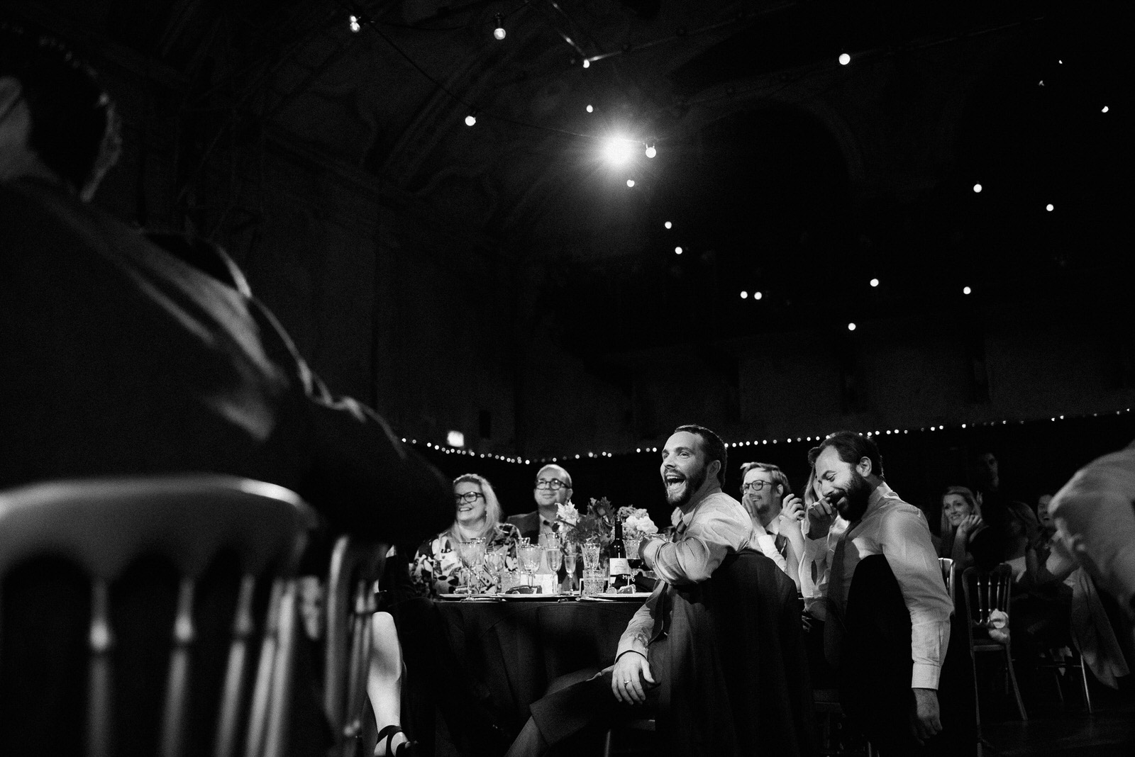 black and white photographs of London couples friends laughing during speeches at Battersea Arts Centre wedding