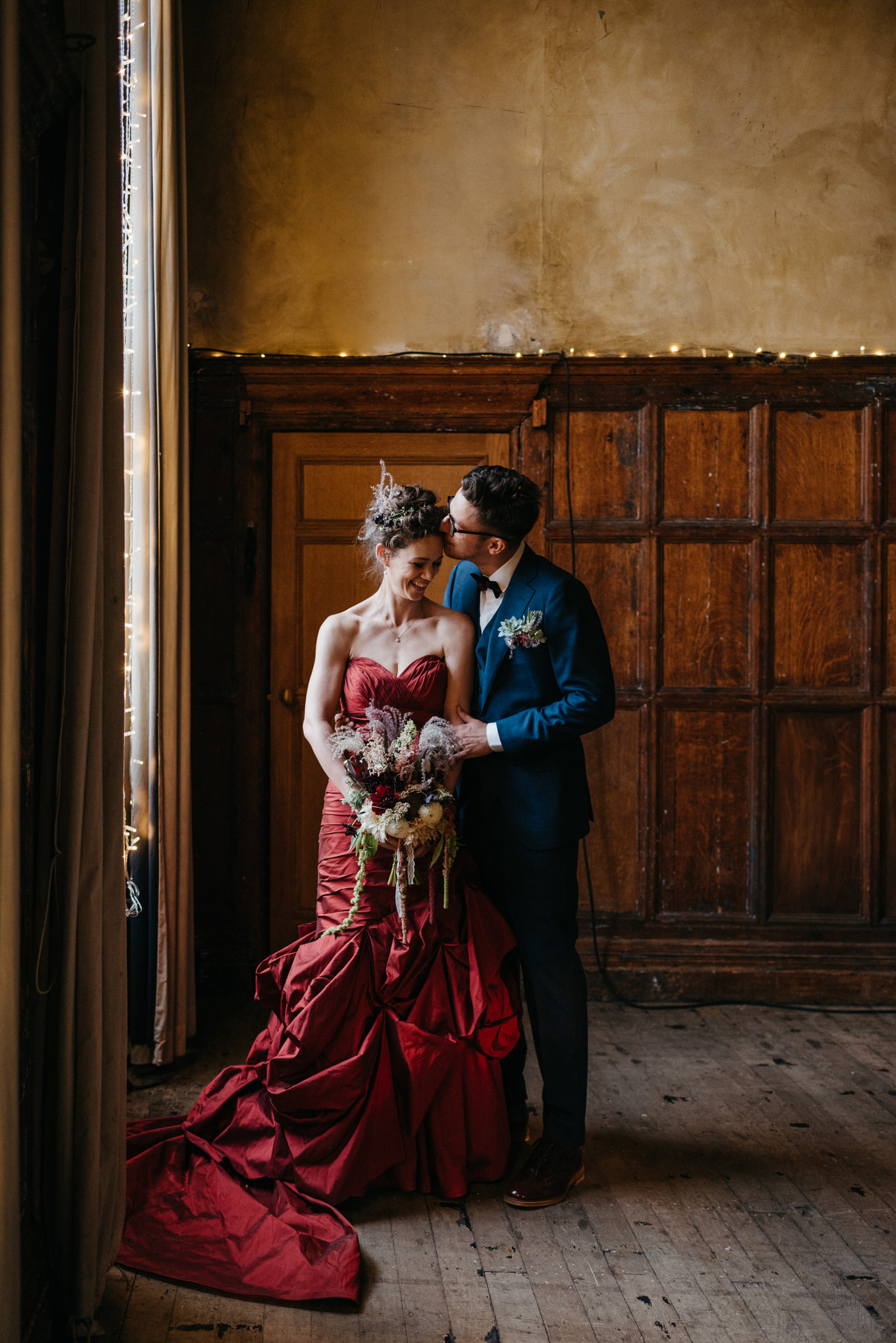 creative bride and groom stand by window at their Battersea Arts Centre wedding in summer