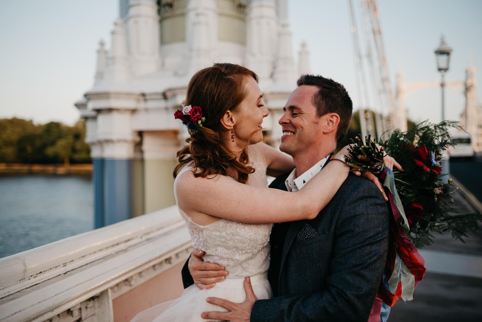 Couple laugh on The Albert Bridge at sunset