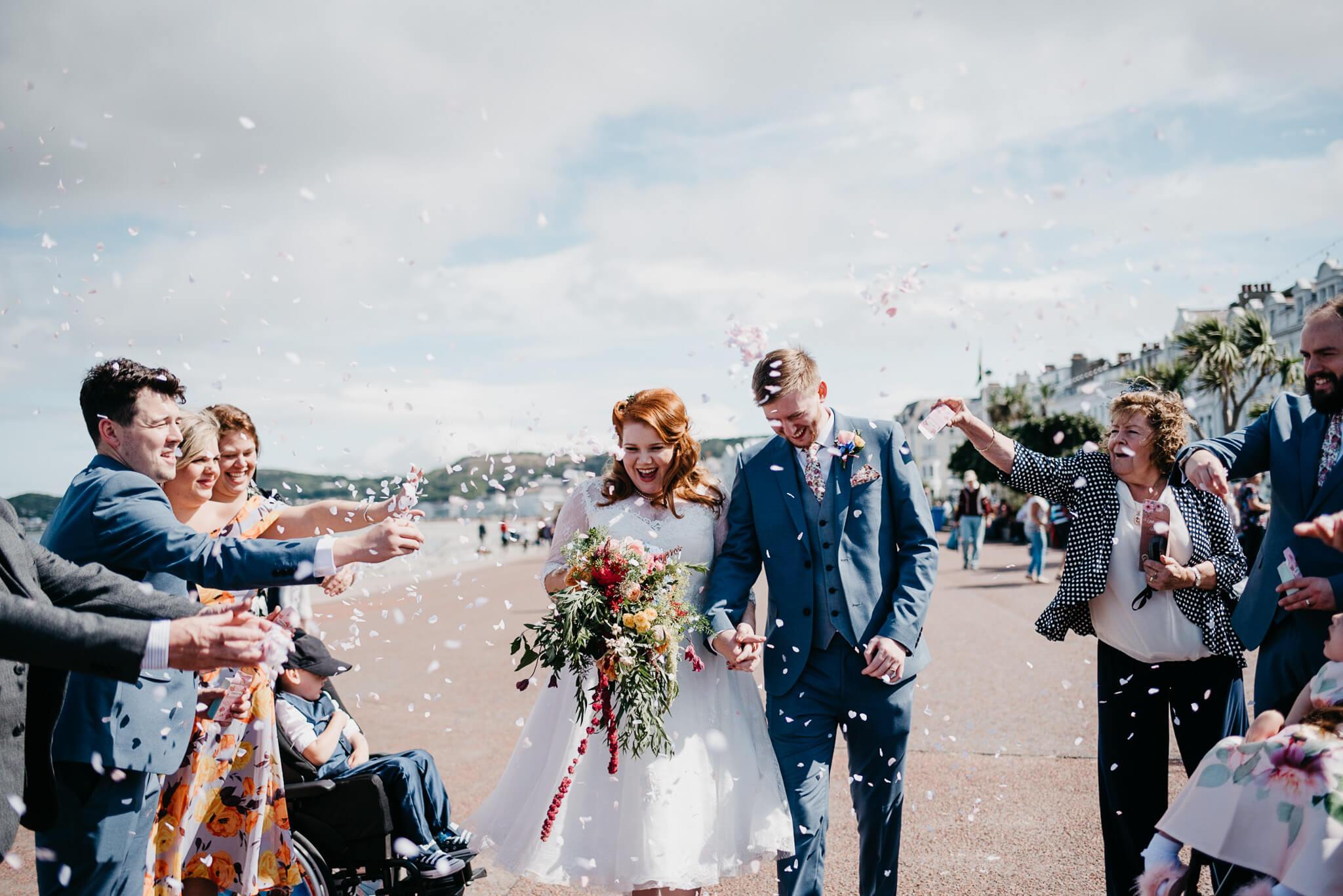 alternative couple walk through confetti throw at Llandudno Promenade