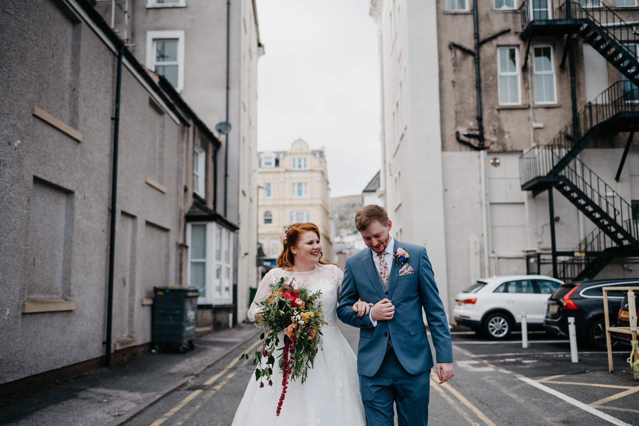 alternative couple walk through city streets during their wedding portraits