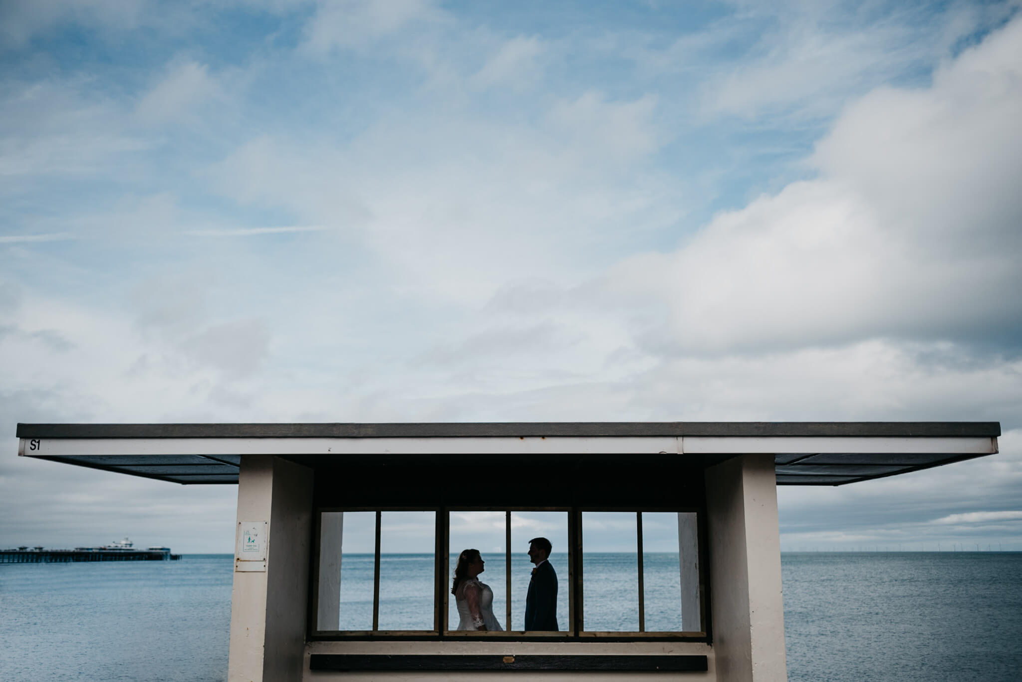 creative portrait of bride and groom at seafront in north wales