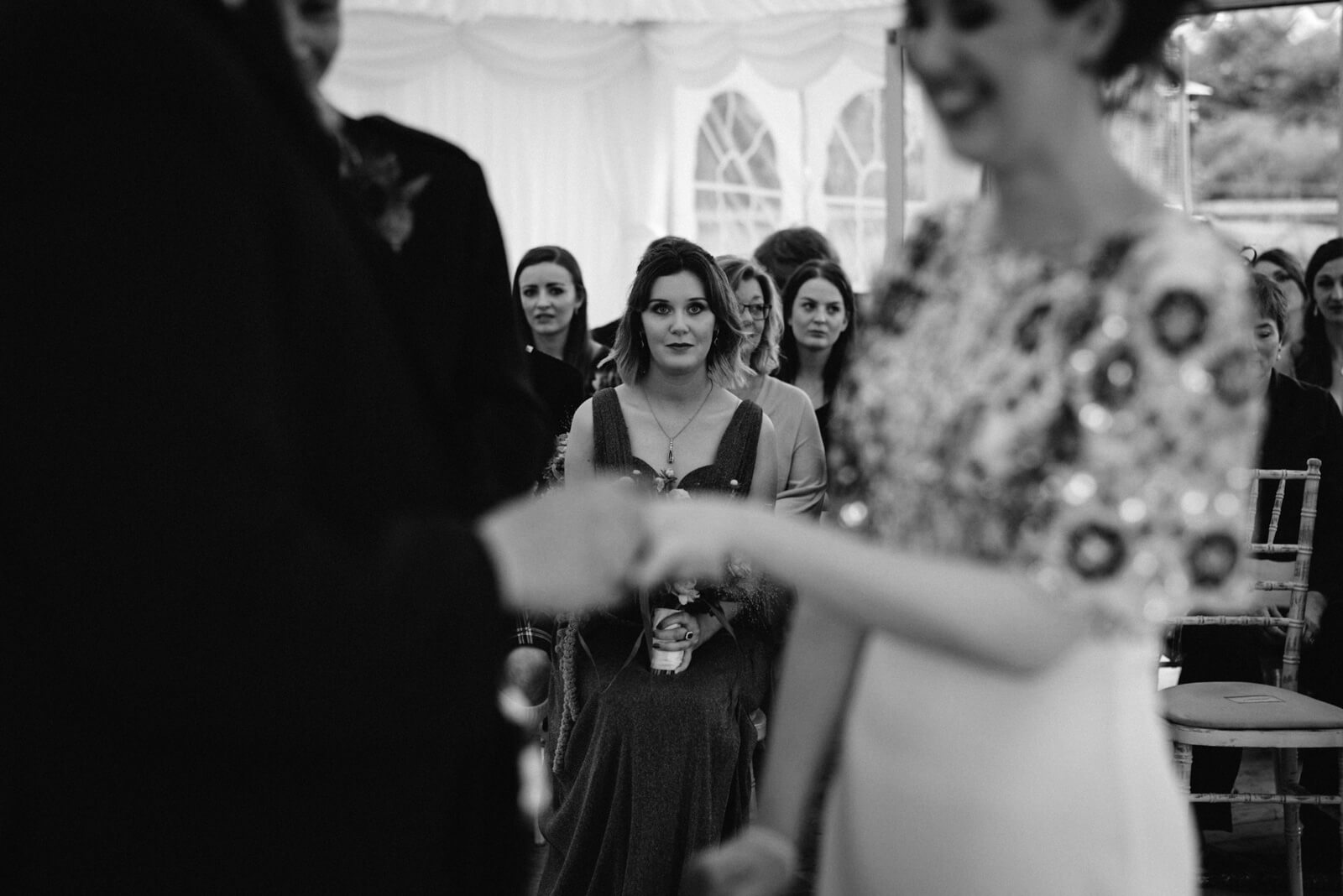 black and white photo of brides sister looking on while bride and groom exchange vows