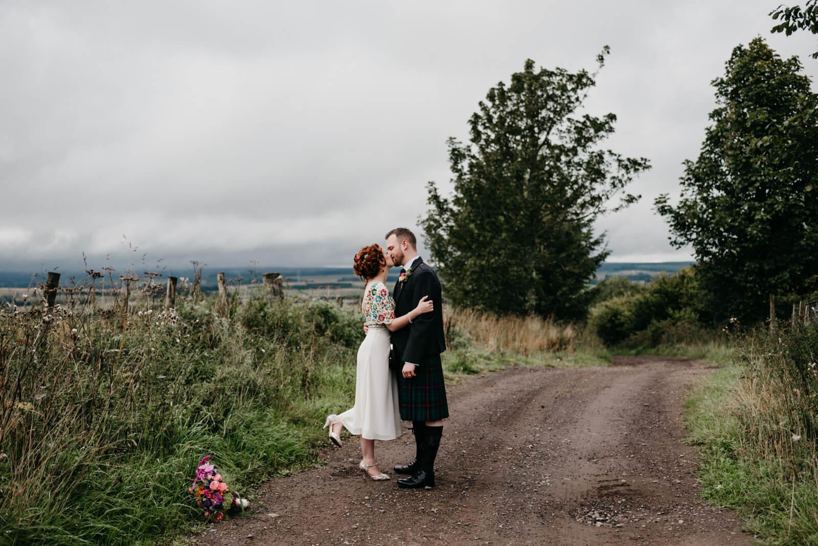 Stirling bride kisses groom during portrait session on Dunblane farm track