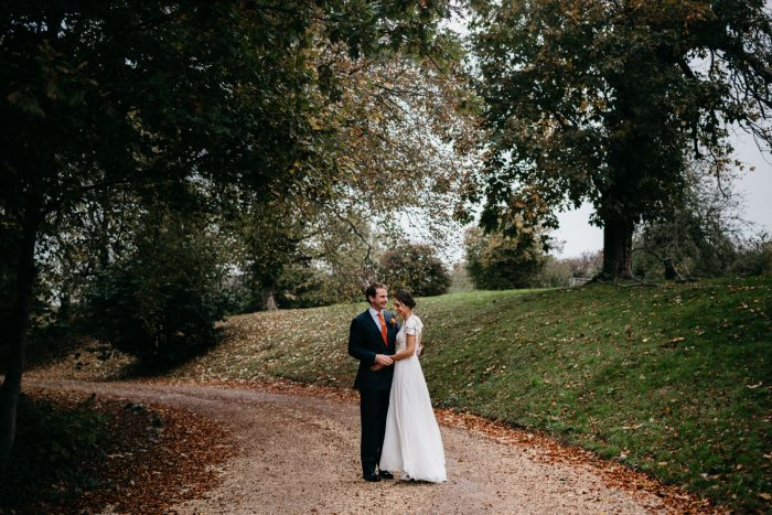 bride and groom stop for photos in the grounds of St Tewdrics House in Chepstow
