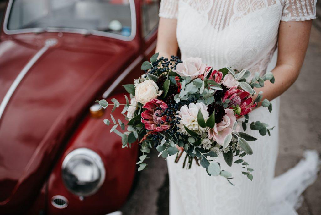 detail photograph of brides bouquet while she stands next to class VW Beetle at Bodnant Food Centre Wedding in Wales