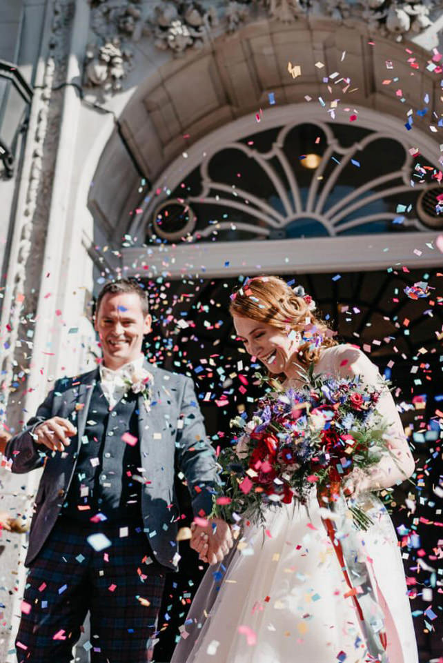 Couple on steps of registry office during colourful and fun confetti throw