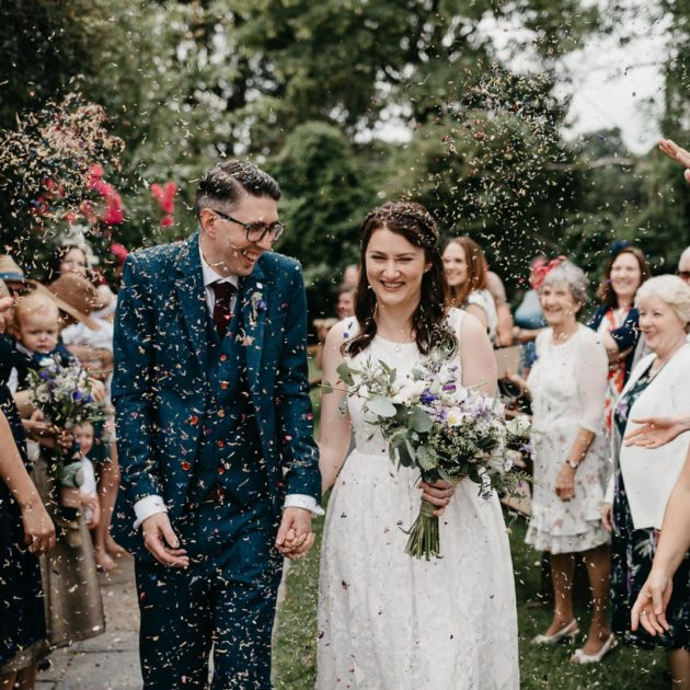 bride and groom walk through confetti after their wedding ceremony at Ceridwen Centre