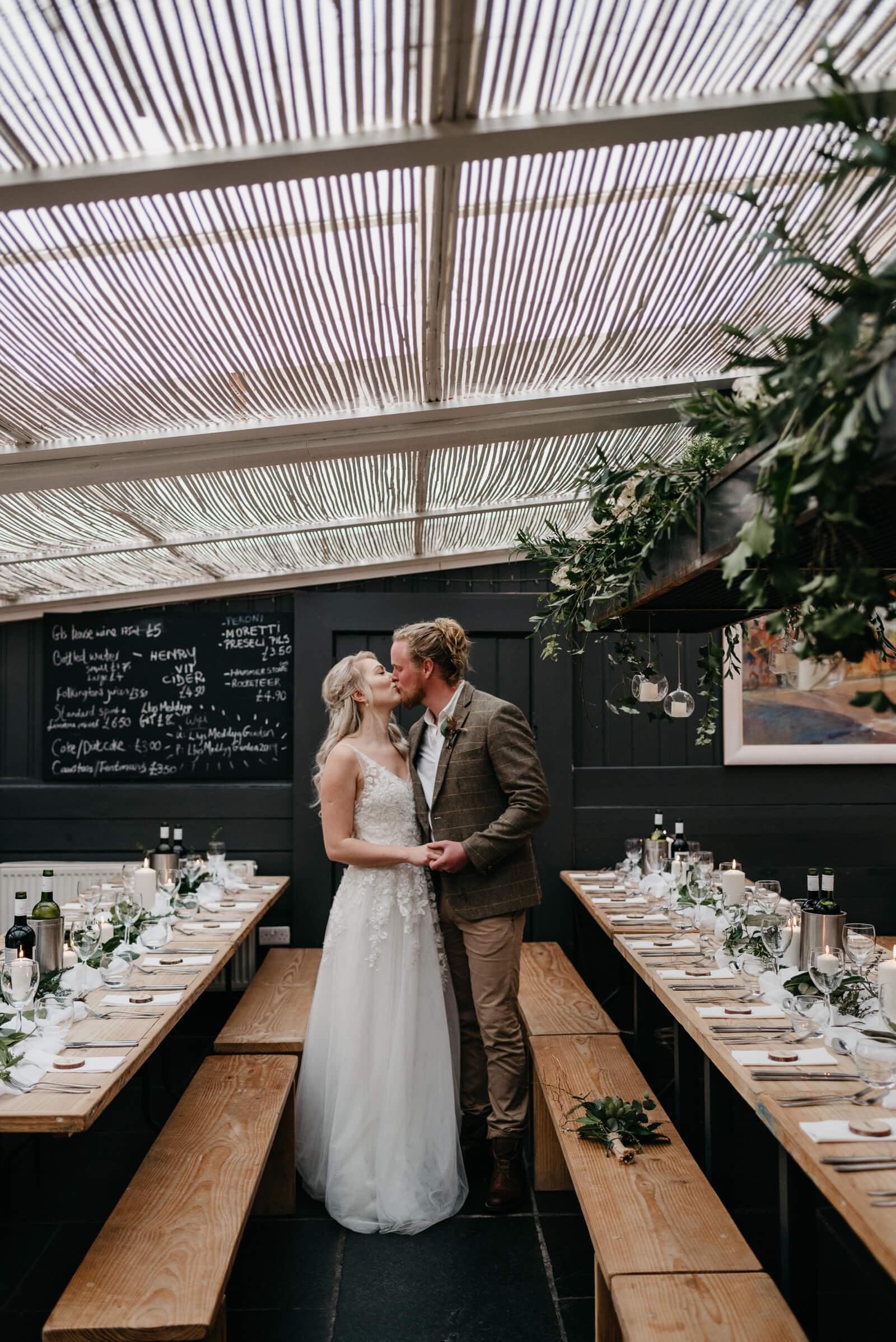 Bride and Groom kiss in Pembrokeshire wedding venue Llys Meddyg
