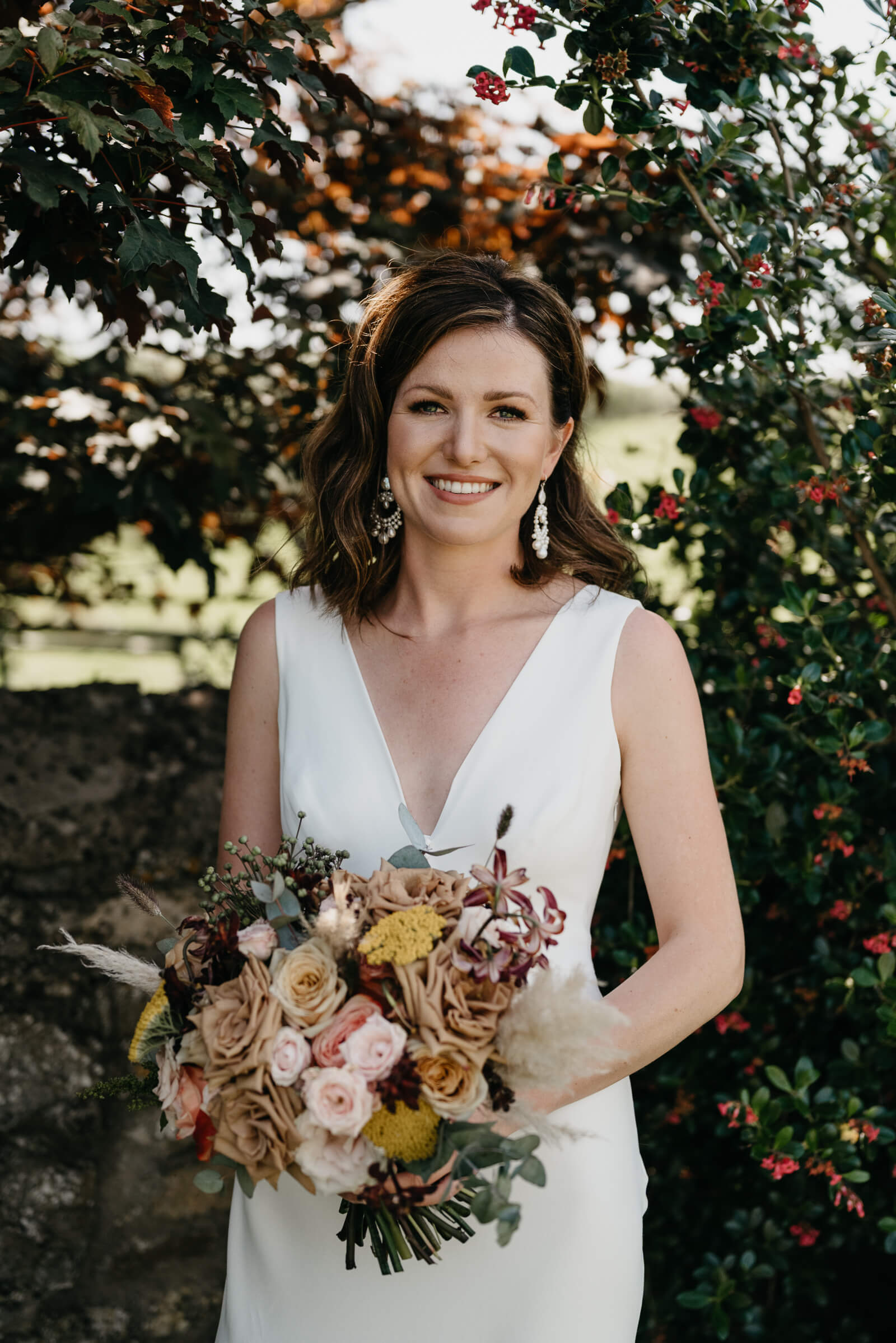 Radiant bride with flowers poses for photograph at Rosedew Farm Wedding venue in Llantwit major