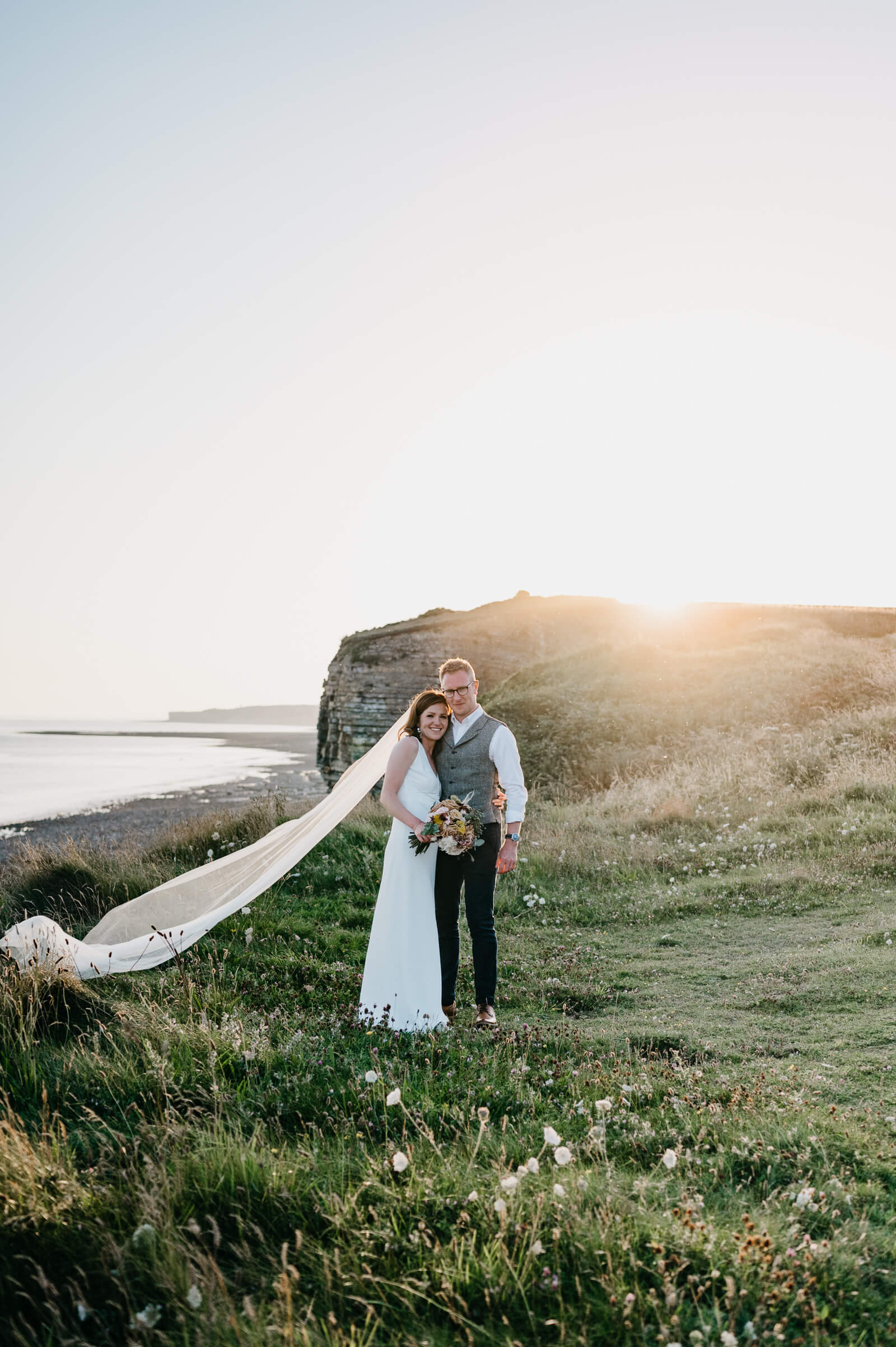 Rosedew Farm bride and groom pose at sunset looking west along the coastline towards Nash Point